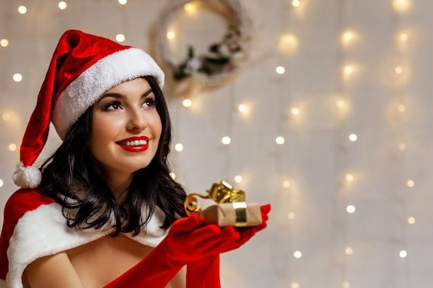 Bella ragazza sexy che indossa abiti di babbo natale con scatola regalo di natale