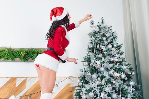 Bella ragazza sexy che indossa abiti di babbo natale. giovane donna che decora l'albero di natale con palline d'argento a casa. vista dal culo sul bel culo di una bella ragazza in mutandine rosse.