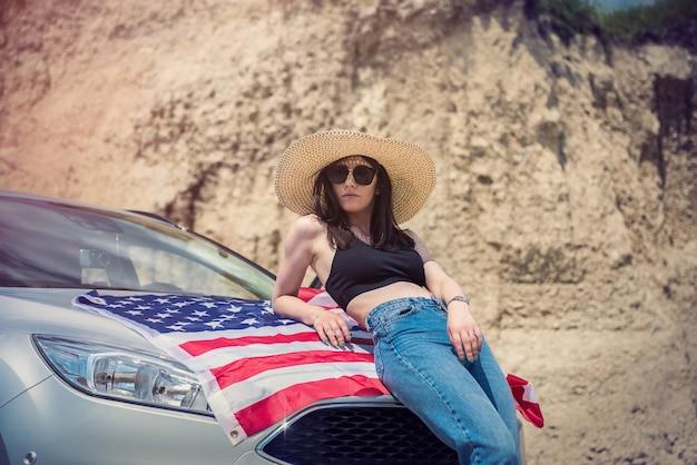 Bella ragazza sexy con bandiera americana e occhiali da sole vicino all'automobile nella cava di sabbia
