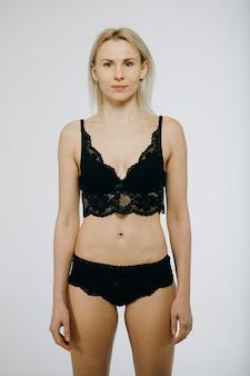 Bella ragazza sexy con i capelli lunghi in un costume da bagno nero, in posa su un bianco