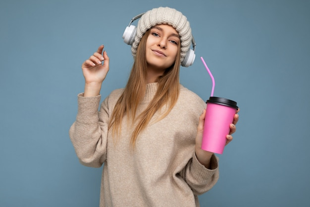 Bella giovane donna bionda sorridente positiva sexy che porta maglione e cappello beige di inverno isolati