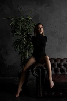 Bella donna sexy sul divano in pelle in camera oscura