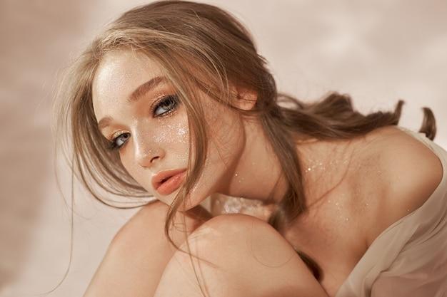 Bella donna sexy seduta sul pavimento, cosmetici e trucco sul viso e sul corpo della ragazza