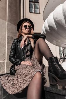 Bellissimo modello femminile giovane sexy in una giacca elegante nera e vestito alla moda con un cappello vintage e occhiali da sole si siede in città in una giornata di sole. donna dallo stile casual e dalla bellezza