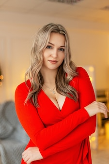 Bella ragazza sexy in un vestito sexy rosso alla moda in una stanza a una festa di natale