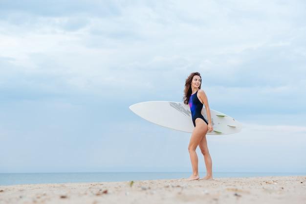 Bella ragazza sexy del surfista che cammina sulla spiaggia