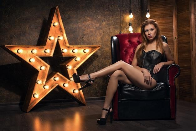 Bella giovane donna sexy sullo sfondo di una stella con lampade