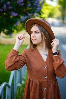 Bella ragazza formosa dai capelli lunghi nel cappello su uno sfondo di fiori lilla