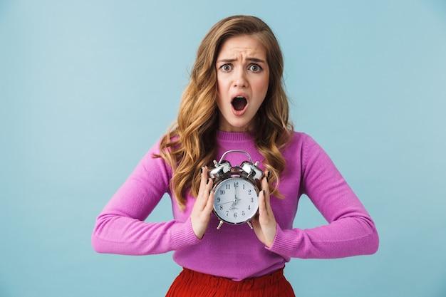 Bella ragazza scioccata confusa che indossa abiti casual in piedi isolata sul muro blu, mostrando la sveglia