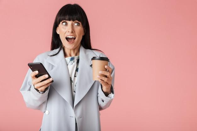 Una bella donna felice scioccata in posa isolata sul muro rosa chiaro usando il telefono cellulare che tiene il caffè.