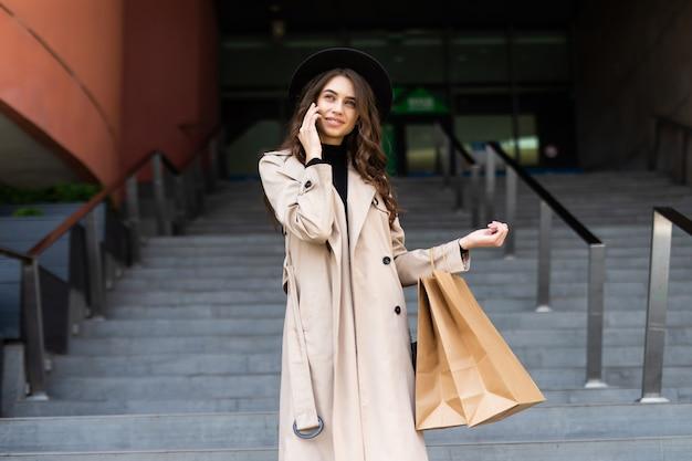 Bella donna dello shopping parlando al telefono sul centro commerciale