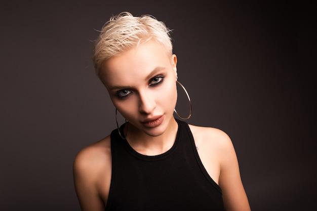 Bella bionda dai capelli corti su una parete grigia. la ragazza con uno sguardo sospettoso.