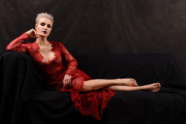 Bella giovane donna bionda dai capelli corti in abito di pizzo rosso sdraiato sul divano