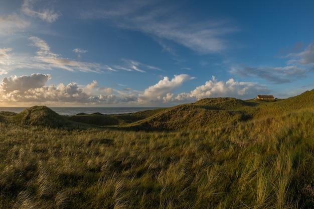 Bellissimo scatto di campi verdi e una casa di campagna in cima a una collina con vista sull'oceano