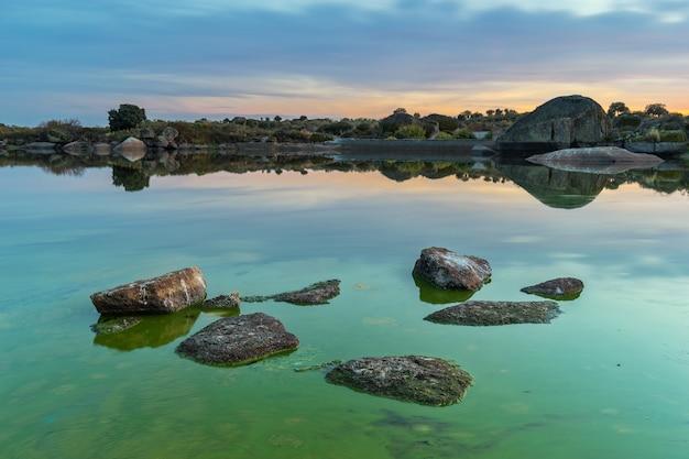 Bello scatto di un laghetto verde con rocce a barruecos, spagna