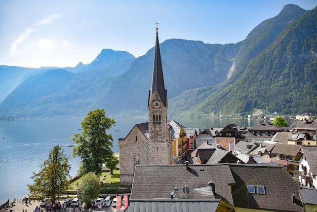 Bellissimo scatto del villaggio di hallstatt in austria circondato da montagne ricoperte di verde