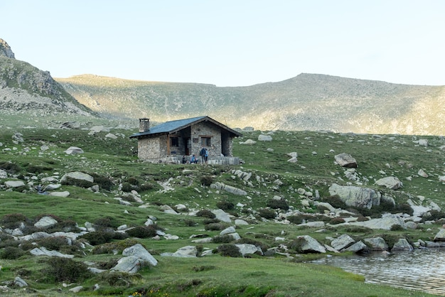 Bello scatto di una piccola casa in un paesaggio di montagna sotto la luce del sole