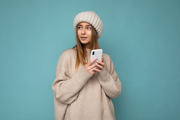 Bella timida giovane donna bionda che indossa un maglione caldo beige alla moda e caldo inverno lavorato a maglia