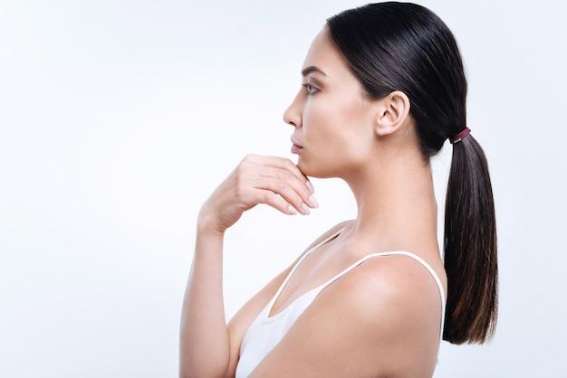 Bella silhouette. la vista laterale di una bella donna dai capelli scuri con una coda di cavallo che posa contro un muro bianco e si tocca il mento
