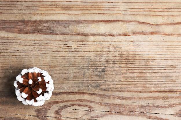 Bellissimo sfondo invernale semplice con pigna su struttura in legno