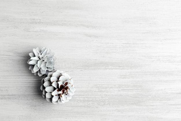 Bellissimo sfondo invernale semplice con pigne su struttura in legno