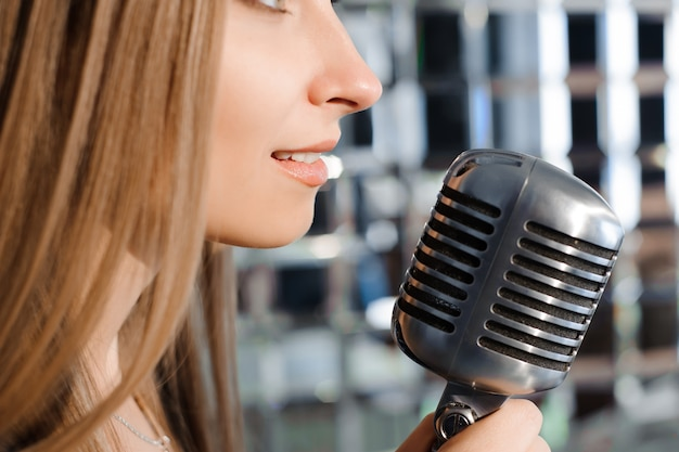 Bella ragazza che canta. bellezza donna con microfono. glamour model singer. canzone karaoke.
