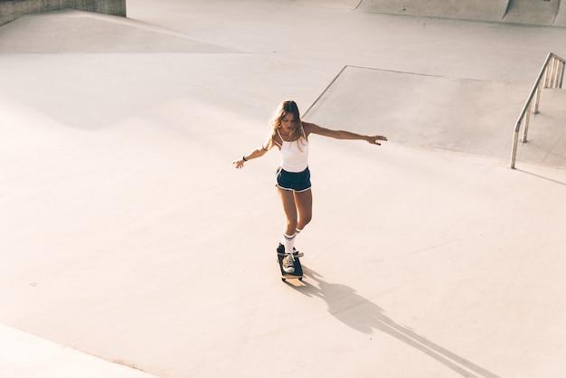 Momenti di lifestyle di bella ragazza skater in uno skatepark