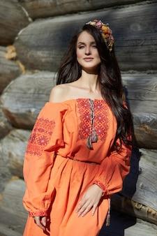 Bella donna slava in un vestito etnico arancione e una corona di fiori sulla sua testa. bellissimo trucco naturale. ritratto di una ragazza russa