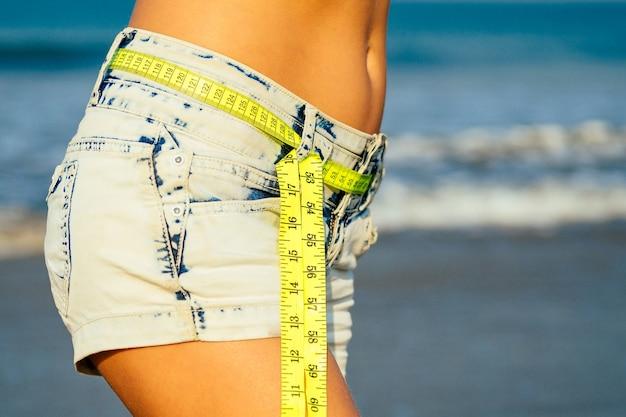 La ragazza bella e snella in pantaloncini di jeans tiene in mano un nastro giallo di misurazione sulla spiaggia. concetto di disintossicazione e dieta