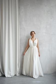 Bella donna snella in abito da sposa bianco, nuova collezione di abiti per la sposa. rumore, fuori fuoco