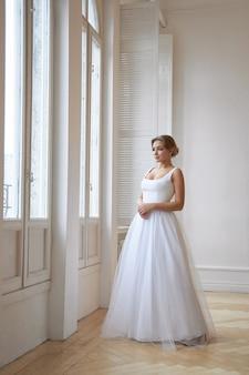 Bella donna snella in abito da sposa bianco