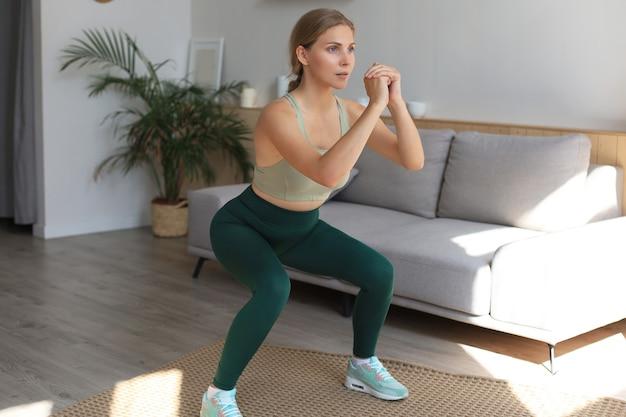 La bella donna esile di forma fisica si accovaccia. sport, stile di vita sano. la ragazza fa sport a casa.