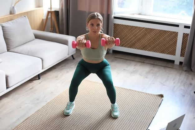 La bella donna sottile di forma fisica si accovaccia con i dumbbells. sport, stile di vita sano. la ragazza fa sport a casa.