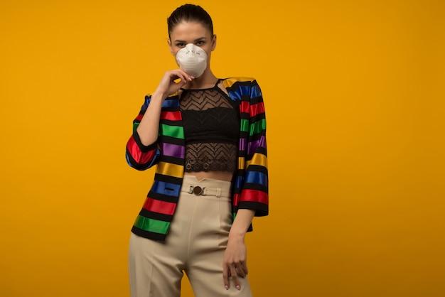 Modello di moda bella ragazza sottile in posa in un respiratore protettivo su uno sfondo giallo. giacca color arcobaleno della comunità lgbt