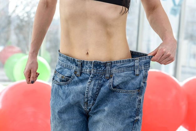 Bella ragazza sottile che mostra il risultato della dieta dopo aver fatto esercizio di fitness