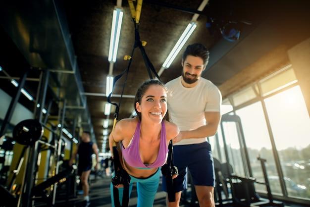 Bella ragazza felice sottile che si esercita davanti al personal trainer sorridente in palestra.