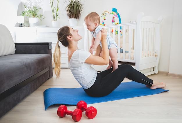 Bella madre magra che gioca con il suo bambino sul tappetino fitness a casa
