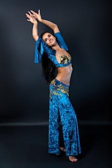 Bella danzatrice del ventre donna sexy snella con lunghi capelli lucidi