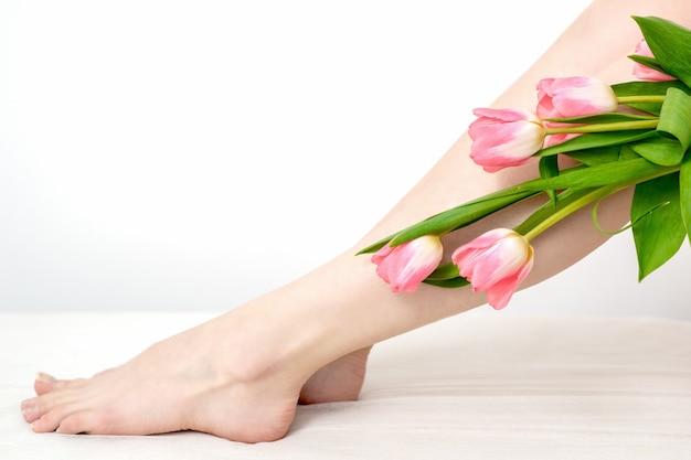 Gambe di bella donna sottile liscia con fiori di tulipani su sfondo bianco