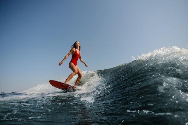 Bella donna esile che pratica il surfing su un'onda blu alta