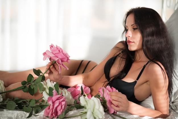 Bella giovane donna castana esile in biancheria intima sexy nera sdraiata a letto e che tiene fiore