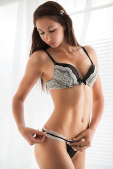 Bella giovane donna castana esile in biancheria intima sexy in bianco e nero in piedi e che ripara le sue mutandine. bellezza del concetto di corpo di donna