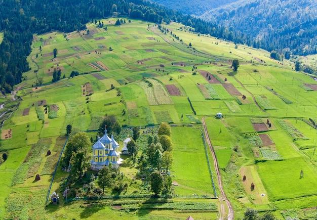 Bella piccola chiesa del villaggio di montagna sul fianco di una montagna (carpazi. ucraina)