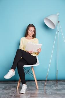 Bella giovane donna intelligente che legge un libro e si siede sulla sedia isolata sullo sfondo blu