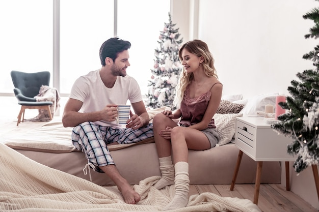 Bel sorriso. barbuto bel giovane con una tazza nel suo sorridente a sua moglie mentre era seduto sul letto