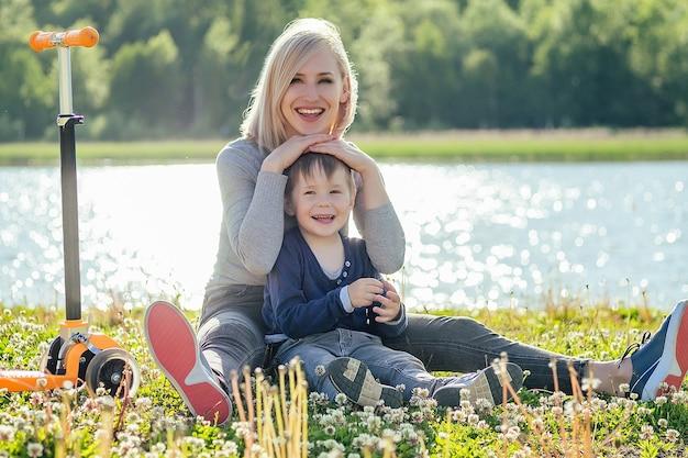 Bel sorriso madre e il suo bambino carino (figlio) seduto sull'erba accanto allo scooter nel parco su uno sfondo di alberi verdi e fiume Foto Premium