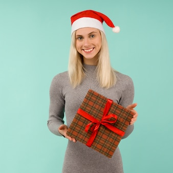 Una ragazza sexy di bel sorriso in cappello di capodanno e vestito grigio tiene in mano i regali