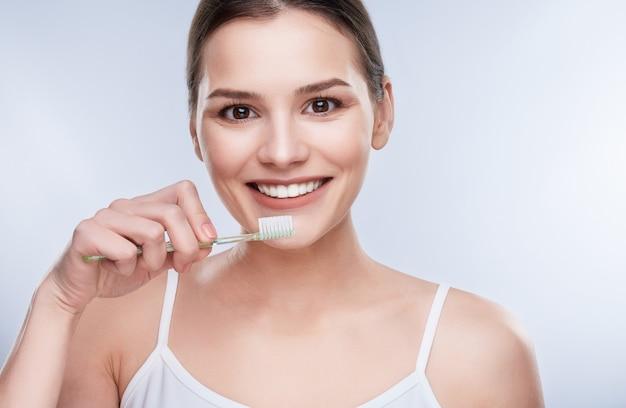 Bel sorriso, denti bianchi e forti. testa e spalle di giovane donna con un sorriso bianco come la neve che tiene lo spazzolino da denti, lavarsi i denti, pulire