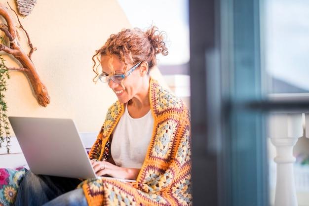Bella donna caucasica sorridente lavora con un computer portatile all'aperto in terrazza. ufficio e stile di vita alternativi lavorare a casa in totale libertà dal solito posto dove le persone lavorano