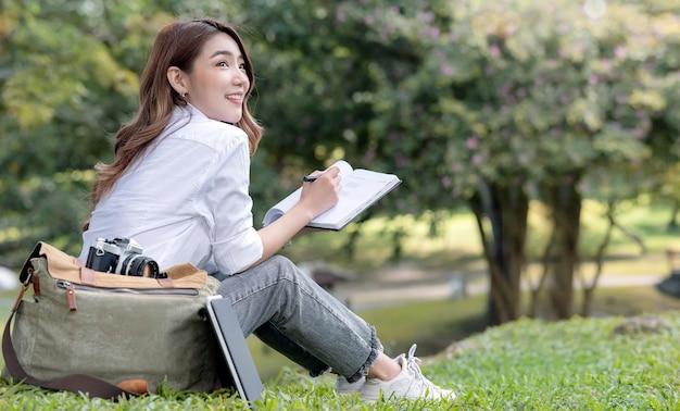 Bello studente universitario sorridente che tiene penna e taccuino che si siede sull'erba verde all'aperto.